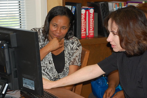 Ellen Moutos-Lee (right) helps a community member