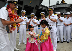 BUSAN, Korea (June 27, 2012) Capt. David Lausman, USS George Washington's commanding officer, presents coins to children dressed in traditional Korean costume during a welcoming ceremony. (U.S. Navy photo by Mass Communication Specialist 1st Class Jennifer A. Villalovos)