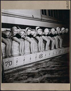"Eight female swimmers from the Ottawa ""Aquamaids"" ready to dive into a pool at an Ottawa YMCA, March 1946 / Huit nageuses d'Aquamaids d'Ottawa prêtes à plonger dans la piscine d'un YMCA d'Ottawa, mars 1946"