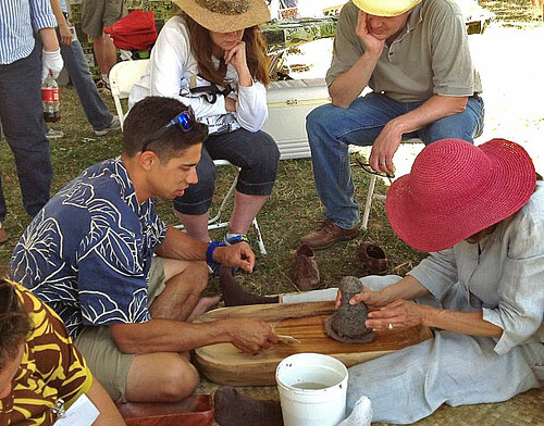 <p>University of Hawaii at Manoa's Ka Papa Lo'i O Kanewai teaches visitors to pound poi at the opening day of the Smithsonian Folklife Festival on June 27.</p>