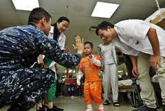 In this file photo, a three-year-old Vietnamese girl high-fives Hospitalman Hector Hernandez during physical therapy aboard the hospital ship USNS Mercy (T-AH 19) in Vinh City, Vietnam, in July 2012 while receiving scar reduction treatment as part of last year's Pacific Partnership mission. (Photo by Kristopher Radder)