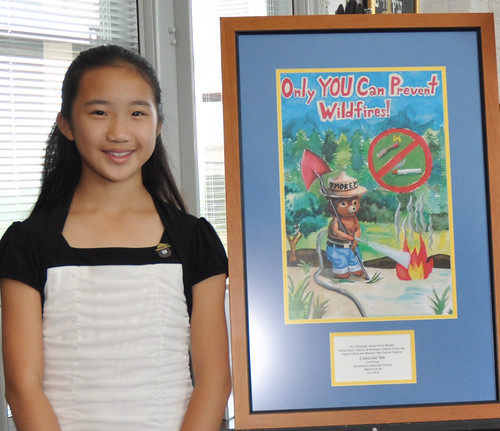 Caroline Tan, 11, of Westfield, N.J., poses with the poster that earned her the title of national winner in the Smokey Bear & Woodsy Owl Poster Contest. Photo credit Dominic Cumberland/U.S. Forest Service