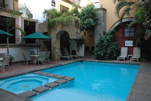 Blue cool swimming pool and jacuzzi, half arch, volcanic stone, tile, bushes, patio furniture, plastic owl, Hotel De Mendoza, Guadalajara, Jalisco, Mexico by Wonderlane