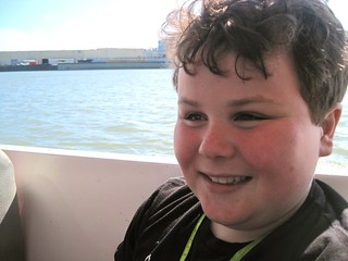 Happy Leo riding an amphibious vehicle, with the  San Francisco Bay in the background
