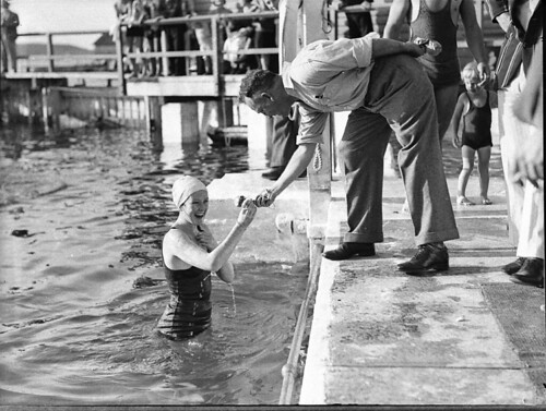 An official hands a young woman swimmer a token, Tramway swimming at Coogee Aquarium, 1935 / photographer Sam Hood