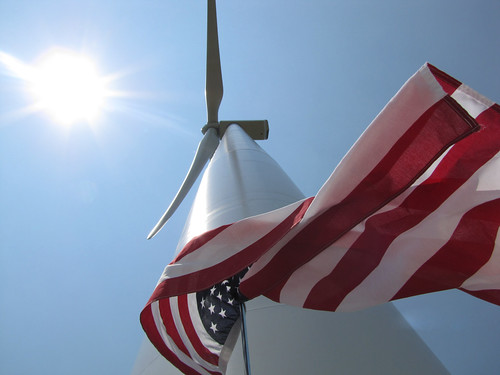 An American flag flies next to a new wind turbine, funded in part through USDA support. USDA photo.
