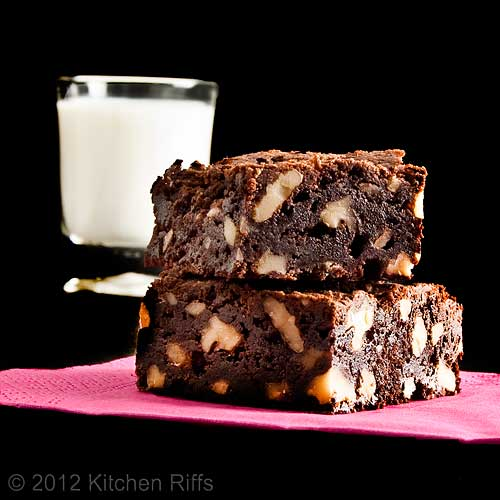 Ultimate Chocolate Brownies on Napkin with Milk, Black Background
