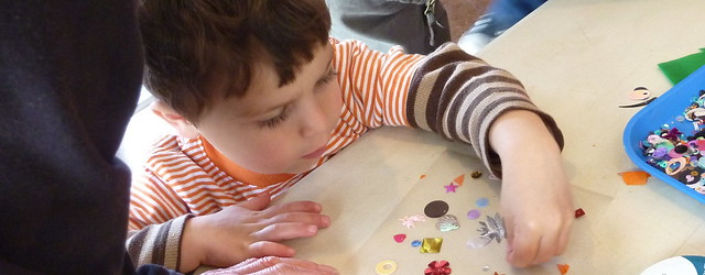 Photo of a little boy choosing glitter for his art piece.