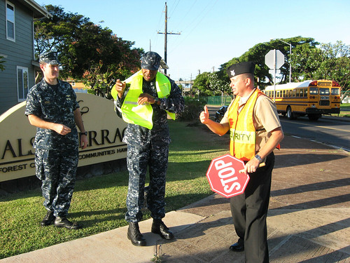 Rear Adm. Frank Ponds serves as an honorary crossing guard, as elementary school students go back to school.