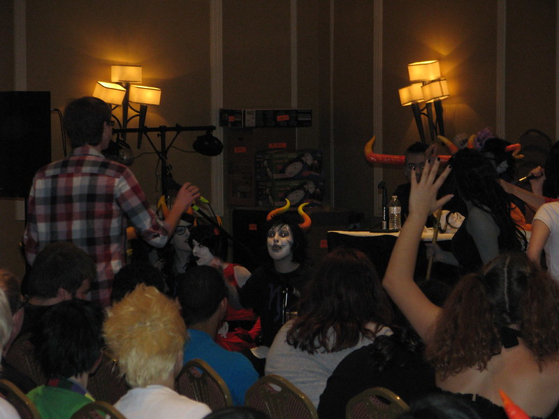 I take the mic to ask the giant panel of Homestuck cosplayers my question. (Photo Credit: Ink)