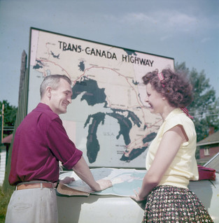 Couple consulting a road map in front of the Trans-Canada highway sign, Ottawa, Ontario / Couple en train de consulter une carte routière devant une affiche de la Transcanadienne, Ottawa, Ontario