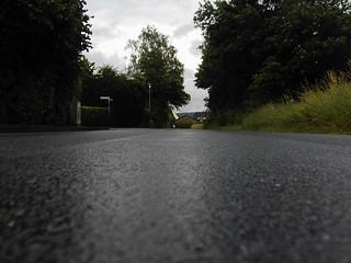Abbildung einer Straße nach einem Regen, aufgenommen auf Bodenebene (Froschperspektive)
