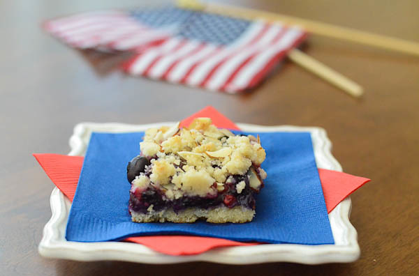 A slice of the Red White and Blue Bars sitting on colored napkins with a small american flag in the background.