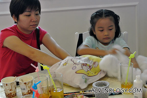 A mum helping her daughter on the stuffing