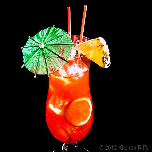 Planter's Punch Cocktails with Pineapple Garnish and Umbrellas, Black Background