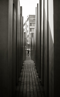 Image of Memorial to the Murdered Jews of Europe near Tiergarten. pillars jewishmonument memorialtothemurderedjewsofeurope denkmalfürdieermordetenjudeneuropas holocaustmemorial berlin mmemorial monument distorted figure bw monochrome holocaustmahnmal history holocaust worldwar2 victims