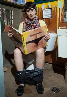 "edie fake sitting on a toilet reading a book entitled ""the big butt book"""