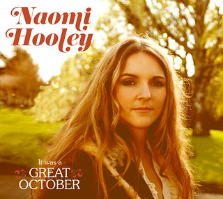 The cover of Naomi Hooley's album, which features a white woman with long blonde hair staring into the camera on a beautiful fall day.