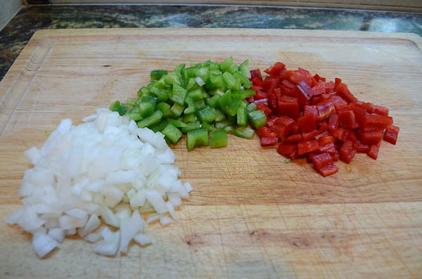 Chopped piles of onions and red and green bell peppers on a cutting board.