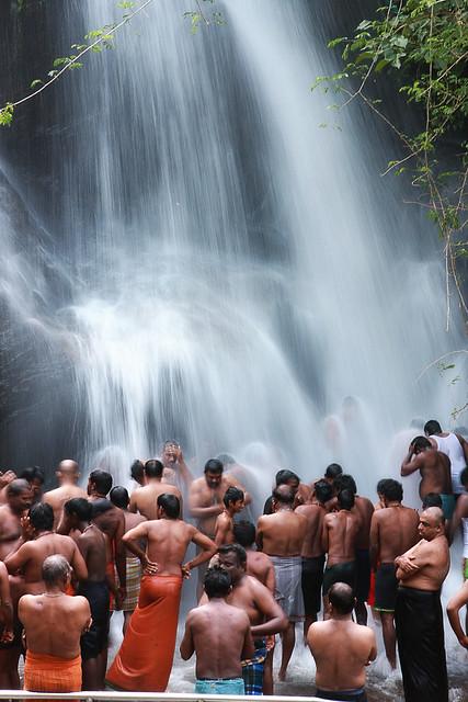 Devotees taking bath in the waterfall Kutralam
