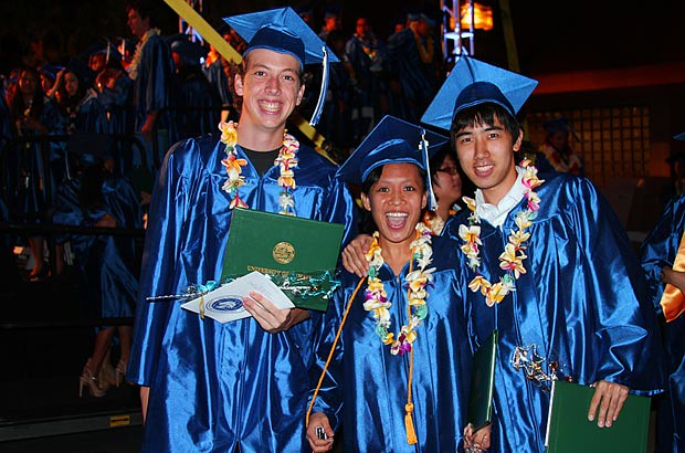 <p>A trio of beaming Kapi'olani Community College graduates</p>