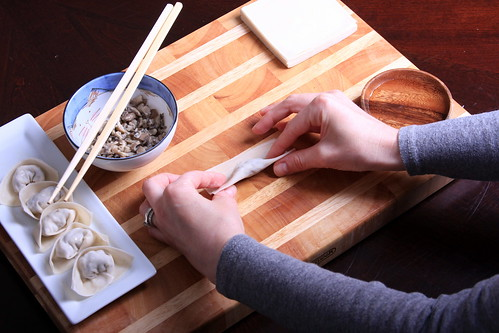 Step Six: Now fold the wonton over again, by lifting up the side that is closest to you and folding it away from you. Don't take your pinched fingers off the sides.