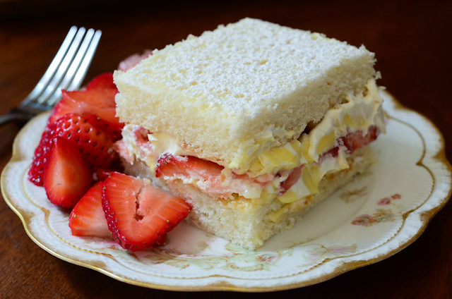 A serving of Strawberries and Cream Cake with strawberries on the side.