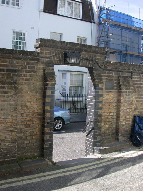 Bronze plaque № 10799 - This boundary wall of the Rutland Estate was destroyed by a bomb during World War II on 25 September 1940.  At the request of residents a right of way was established when the wall was rebuilt by the City of Westminster in 1948 and has become to be known as the 'hole in the wall'  Unveiled on 28 October 1988