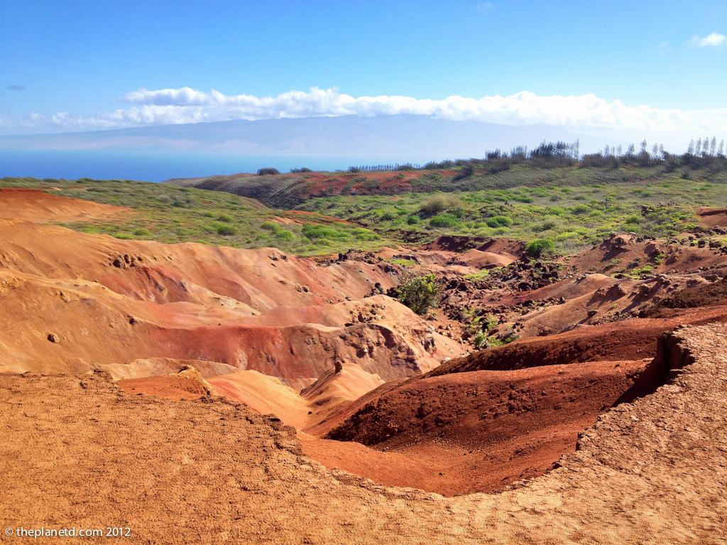 dry land on island of lanai with lush backdrop