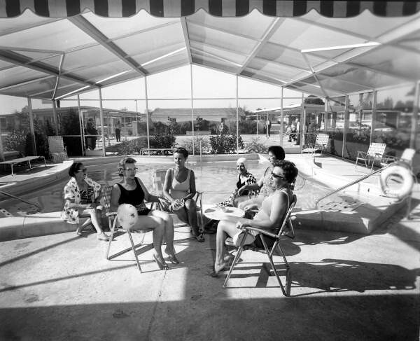 Ladies sit near the community swimming pool: Fort Lauderdale, Florida