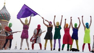 the members of pussy riot standing on a wall wearing bright balaclavas