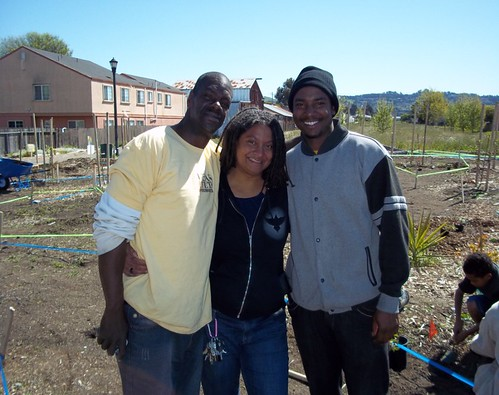 Doria Robinson of Urban Tilth is flanked by staff members during a break of the day-long celebration to plant an Edible Forest in Richmond, Calif.