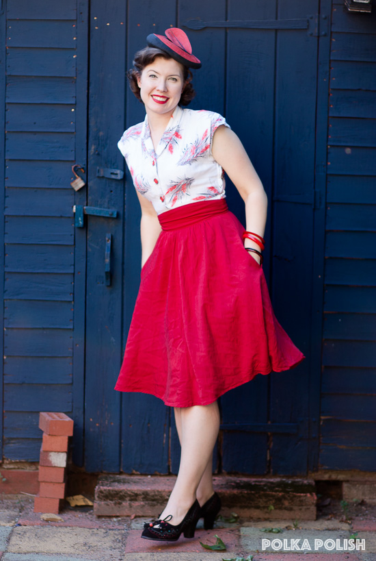 1940s wheat-print dress paired with a red skirt and bulls-eye vintage hat