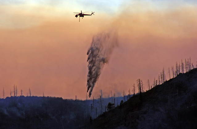 A skycrane drops water on hot spots behind LA mountain in Los Alamos.  Photo by Ethan Frogget.