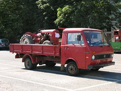 A truck carries a tractor