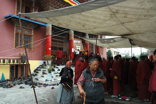 Putting up a portrait of The Great 14th Dalai Lama, Tibetan woman, Buddhist monks, tent, shoes, column, Tharlam Monastery, Lamdre, prayer wheel, Boudha, Kathmandu, Nepal by Wonderlane