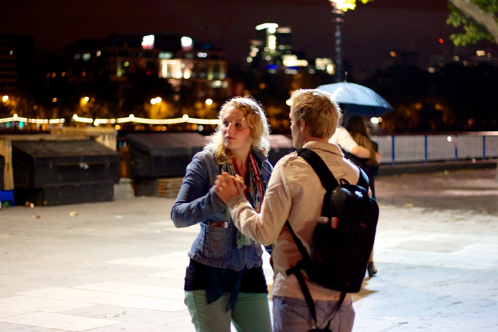 Couples dancing to a busker's tunes under Waterloo bridge