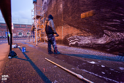 ROA at work on his Shoreditch Hedgehog Street Art Mural