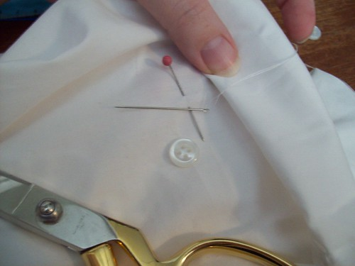 measure half inch up from cuff and stitch button on