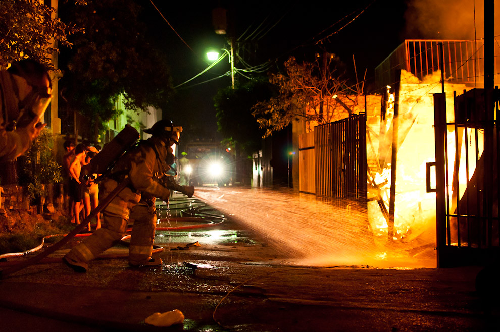 Una mujer bombero suelta el agua sobre las llamas que consumían una carpintería mientras sucedía un feroz incendio en el barrio de la Chacarita en la madrugada del 8 de Marzo pasado. Las compañías que asistieron a este gran incendio fueron la 3ra. Compañía de Sajonia (primeros), el Destacamento Mercado 4 y la 2da. Compañía de Trinidad; además de la colaboración de los bomberos de la Federación (azules). Trabajaron en conjunto para aplacar las fuertes llamas y cuidar que no se extienda por las casas vecinas. En este incendio solo fue afectada una casa y una carpintería, se tomaron todas las medidas necesarias para que el incidente no se agrave. (Elton Núñez)