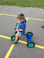 Nate rides his tricycle.