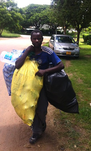 Tomson Chikowero carrying the bags of plastic bottles that he collected from people's trash for recycling. People like him have become Zimbabwe's unlikely climate change ambassadors. Credit: Stanley Kwenda/IPS