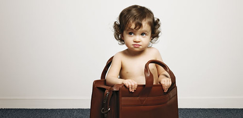 white baby sitting in a briefcase