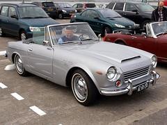 triumph tr250(0.0), triumph tr5(0.0), sunbeam tiger(0.0), triumph tr6(0.0), automobile(1.0), vehicle(1.0), datsun roadster(1.0), antique car(1.0), classic car(1.0), land vehicle(1.0), convertible(1.0), sports car(1.0),