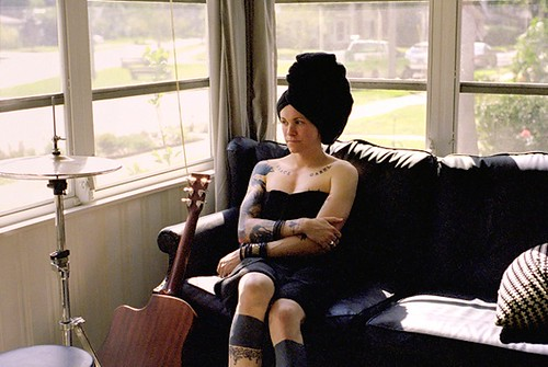 Laura Jane Grace of Against Me! reclines on a couch beside an acoustic guitar. She wears a sleeveless top that shows off her tattoos and her hair is wrapped in a towel.
