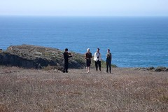 long-distance shot of Michael and her partner at their wedding, standing on a cliff in the sun