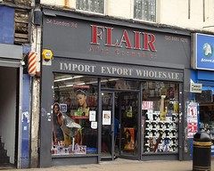 "A terraced shopfront with full-length windows and a glass double door in the middle.  The sign above the frontage reads ""Flair Afro Cosmetics / Import Export Wholesale"".  There are a couple of pictures of Black female models in the left-hand window, and what looks like a display of hairdryer boxes in the right-hand window, underneath a small notice reading ""SALE""."