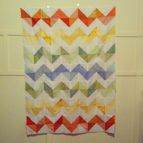 rainbow zig zag quilt top pinned to the wall