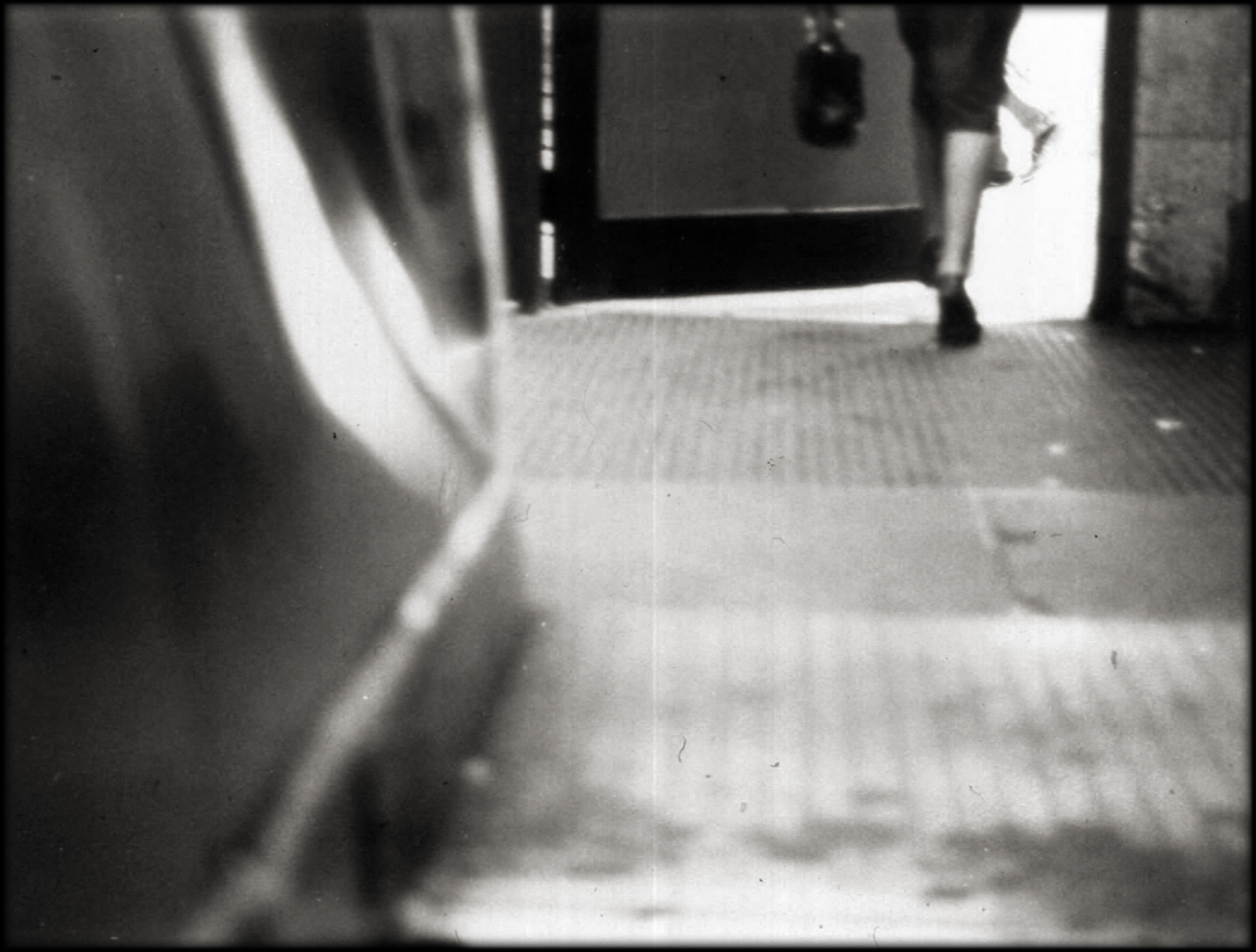 442 - Black and white photograph, seen from the top of an escalator, the back of a woman's legs as she walks thru a door to the outside. She wears a dark dress and dark shoes and carries a dark handbag.