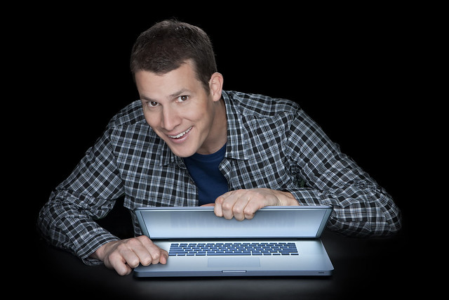 Daniel Tosh looking creepy holding a laptop computer